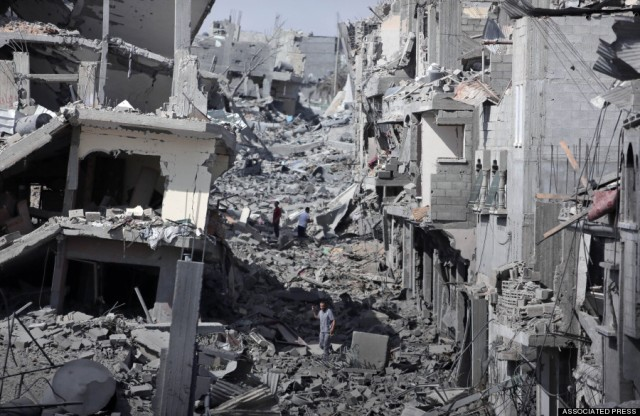 Palestinians inspect the damage of their destroyed houses during a 12-hour cease-fire in Gaza City's Shijaiyah neighborhood, Saturday, July 26, 2014. Gaza residents used a 12-hour humanitarian cease-fire on Saturday to stock up on supplies and survey the devastation from nearly three weeks of fighting, as they braced for a resumption of Israel's war on Hamas amid stalled efforts to secure a longer truce. (AP Photo/Khalil Hamra)