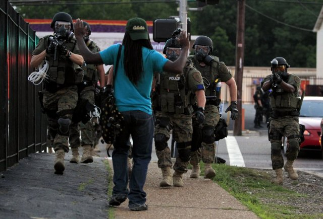Riot police point their weapons at an unarmed man in Ferguson, Source: AP Photos, Jeff Roberson